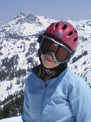 feliciA at kirkwood in a light blue schoeller coat and giro helmet standing in front of the cirque at kirkwood mountain resort.