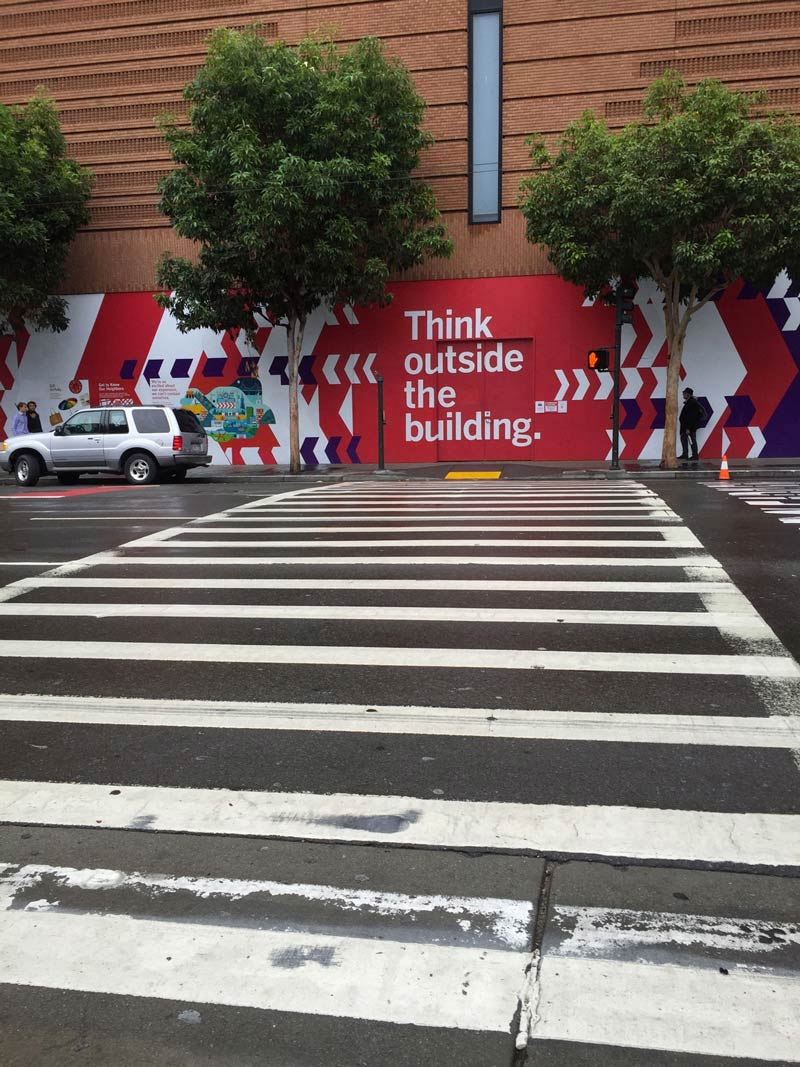 crosswalk shot across from the sfmoma with painting that reads think outside the building.